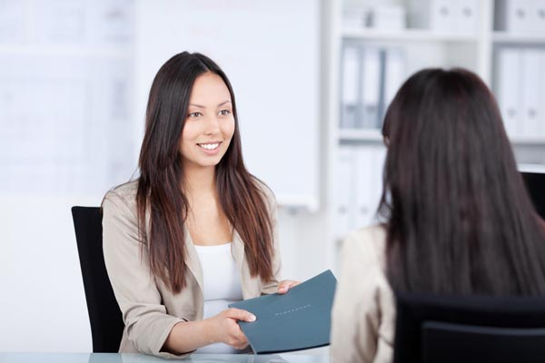 A young woman passes her resume to an interviewer