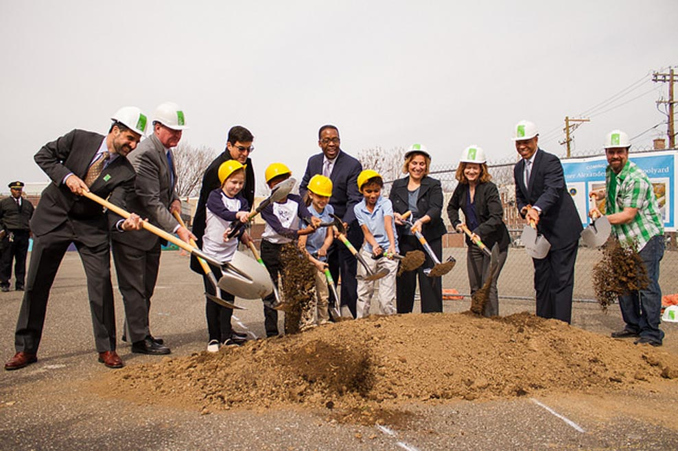 Accounting non-profit workers in hard hats break ground at construction site