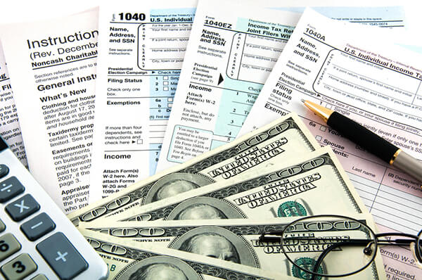 Tax forms, calculator and money.