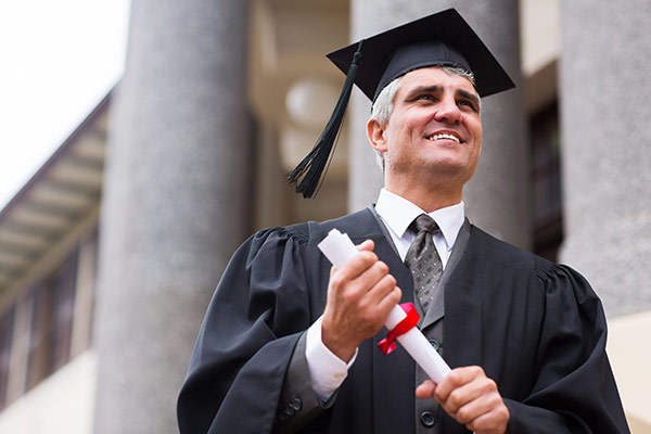 Man graduating online MBA program with diploma.