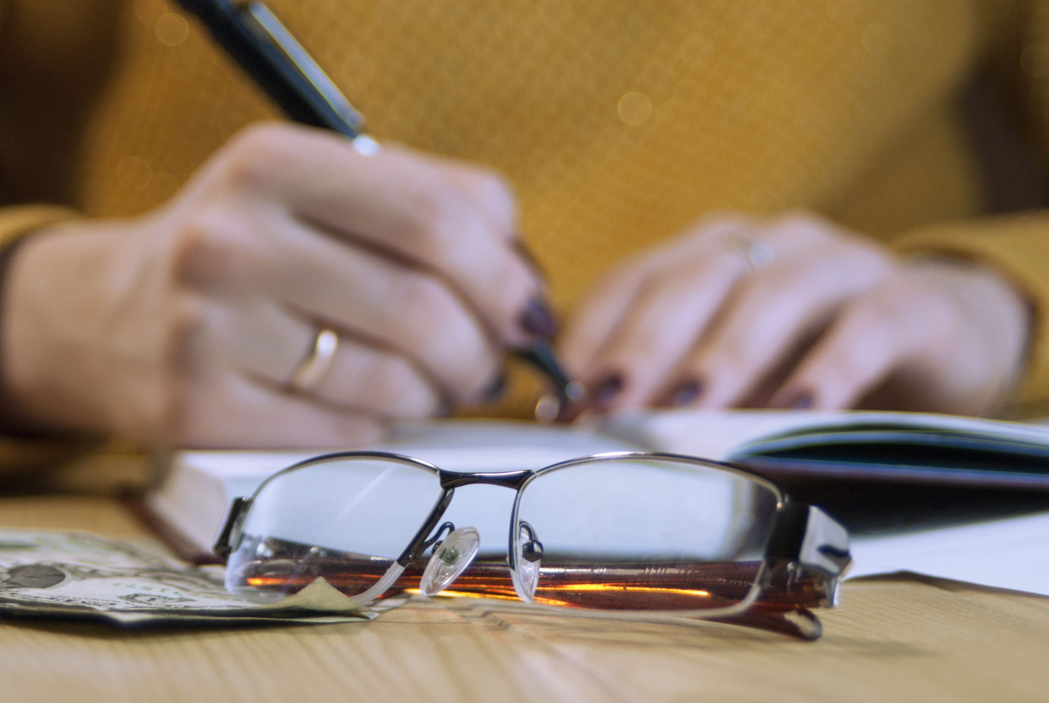 Hands writing in a journal with glasses next to them on a desk.