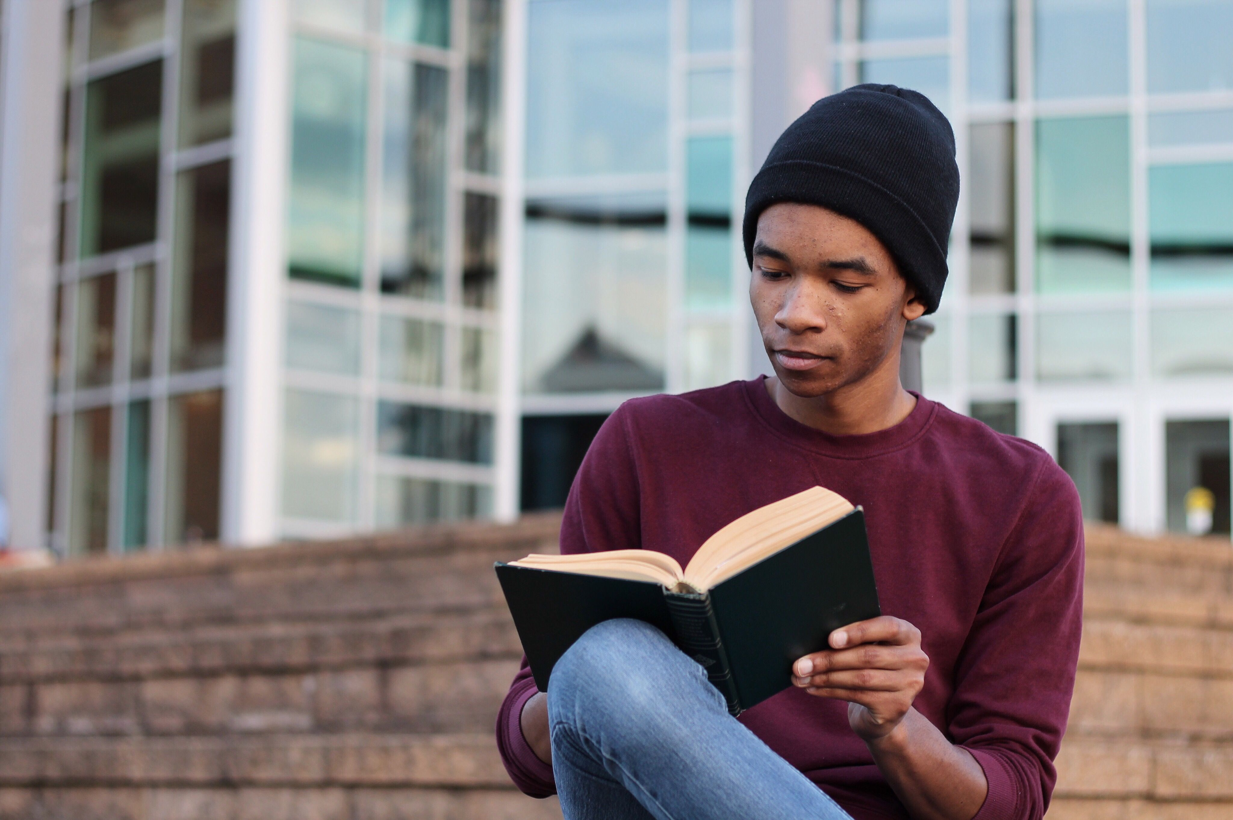 Student reading a book on campus.