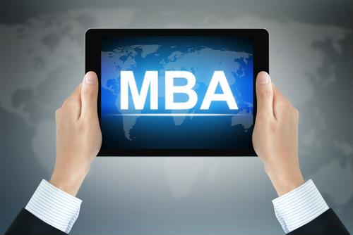 Business professional holding an ipad with the text, MBA on the screen.