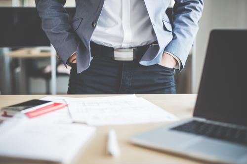 A guy with his hands in his pockets standing in front of a desk