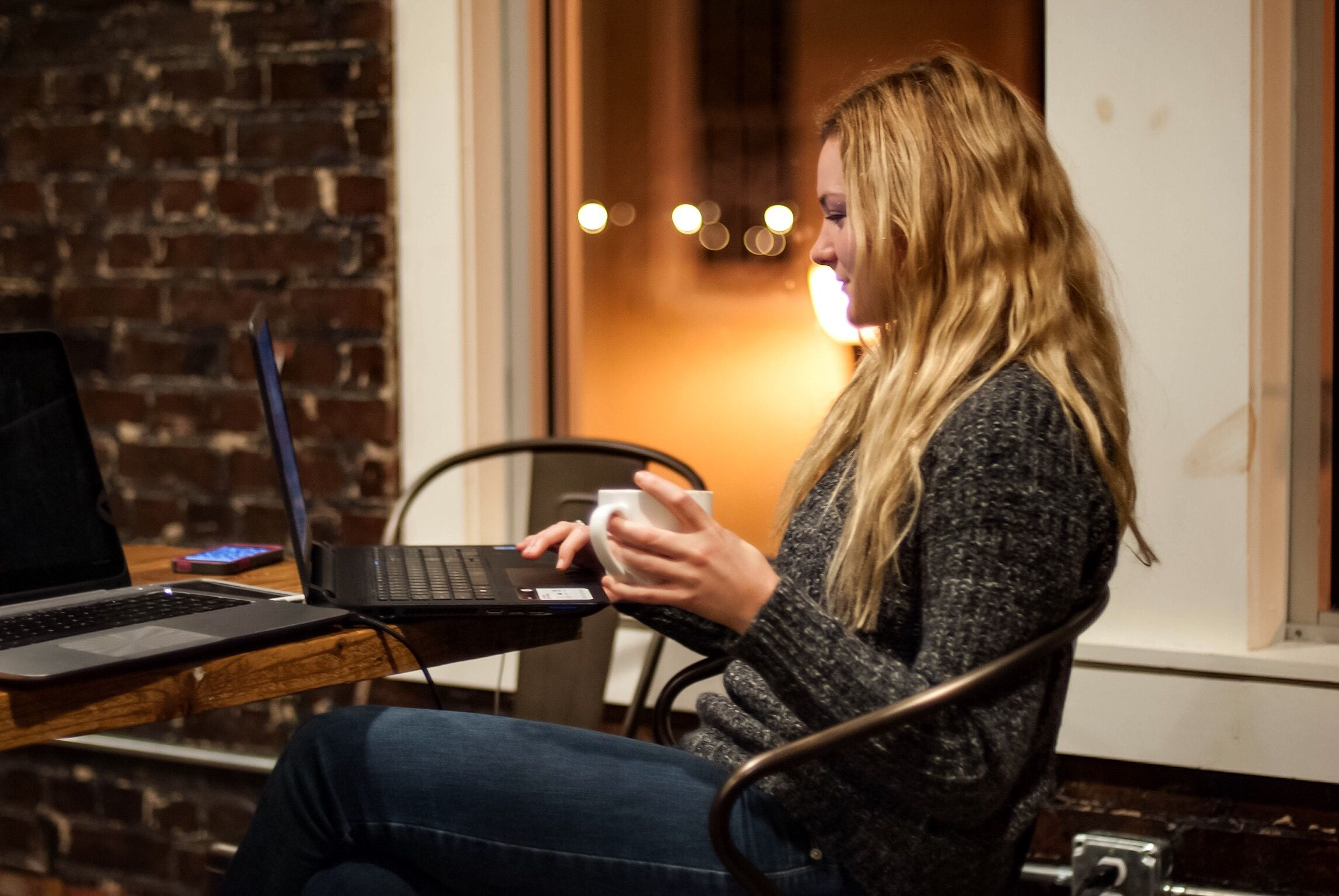 A young woman studies on her laptop while drinking a cup of coffee